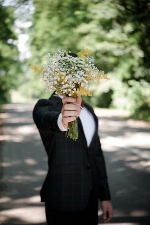 Man with floral bouquet in front of face