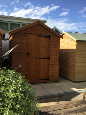 A heavy duty timber shed with single door and side window