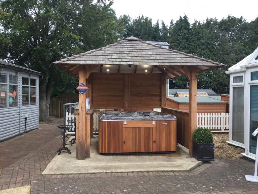 Cedar shingle gazebo with open sides providing cover for hot tub