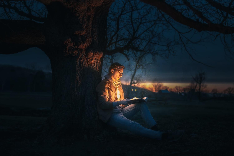 man reading book under tree