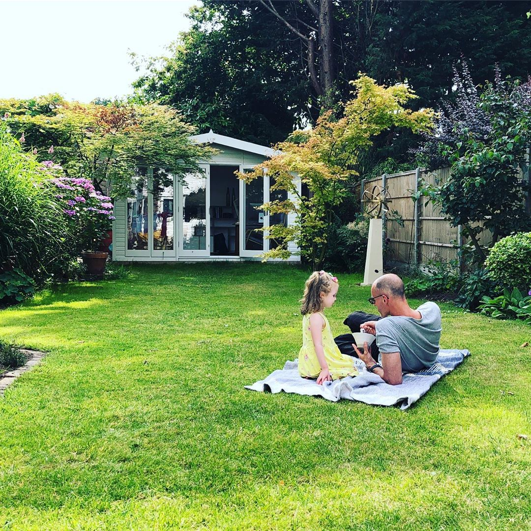 Father and daughter on picnic rug on lawn in front of garden studio