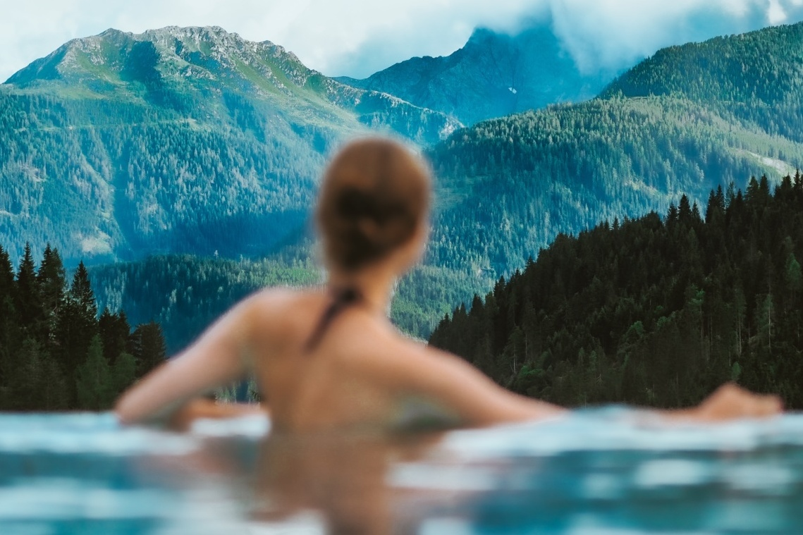 Woman wild swimming while looking at view of mountain