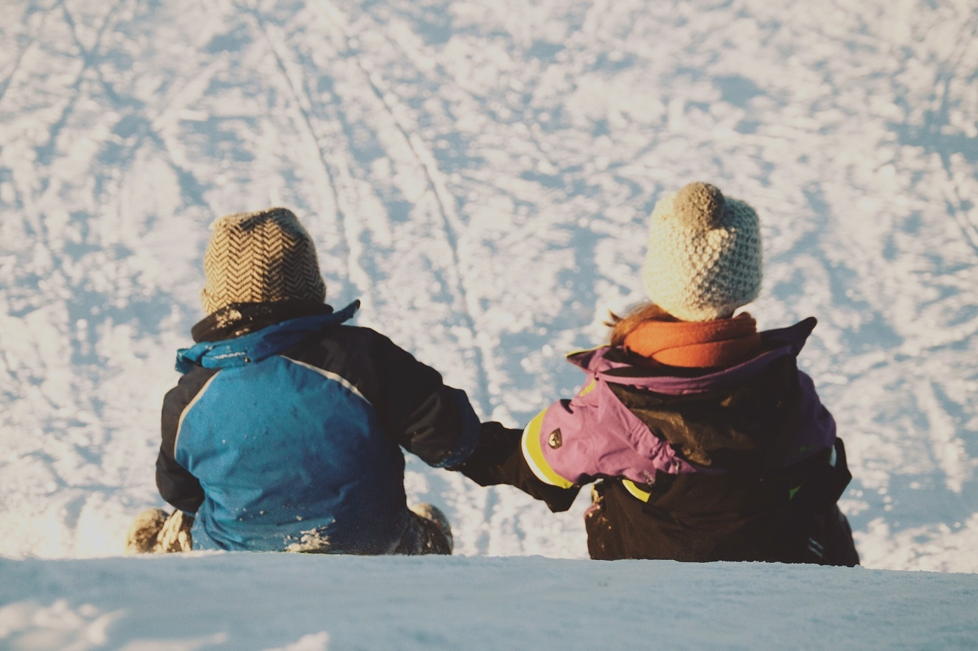Two small children in winter clothes about to sledge down a snowy bank