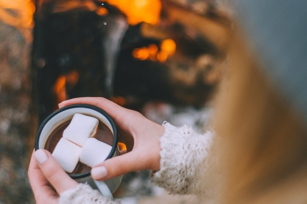 Hands around a mug of hot chocolate with marshmellows with fire pit in background
