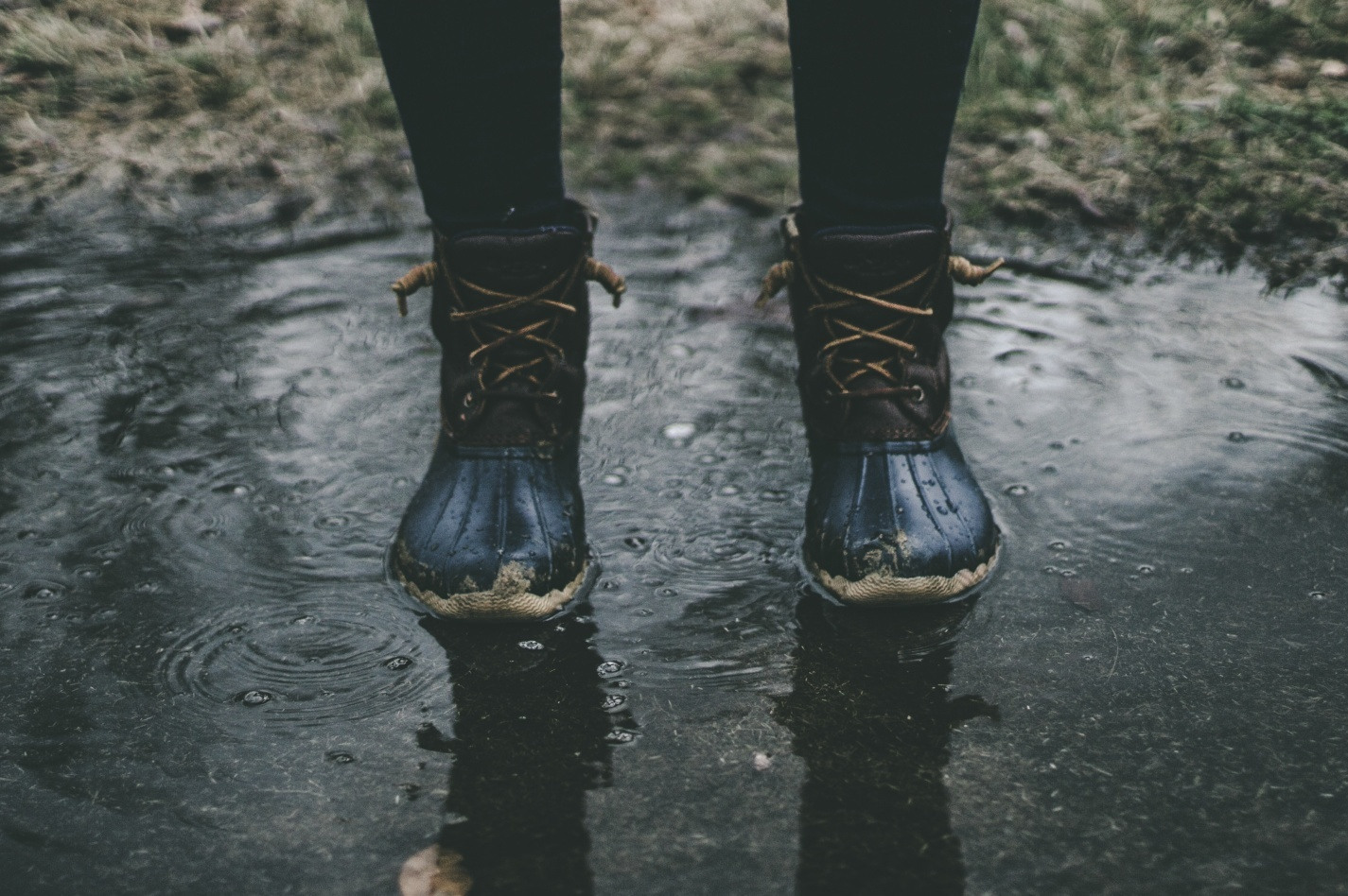 Close up on a person wearing wellington boots standing in a puddle