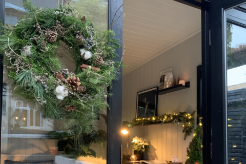 A Christmas wreath hangs on the glass door of a painted garden studio. Inside, there are fairy lights and candles and you can see the styling is Christmassy