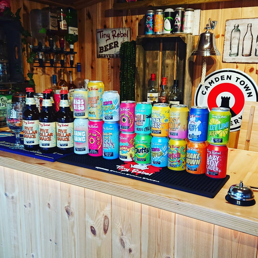 Multiple cans and bottles of beer standing on a wooden bar in a garden room.