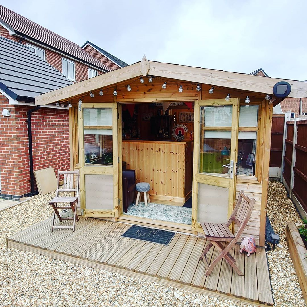 A garden studio with a wooden decking and foldable deckchairs.