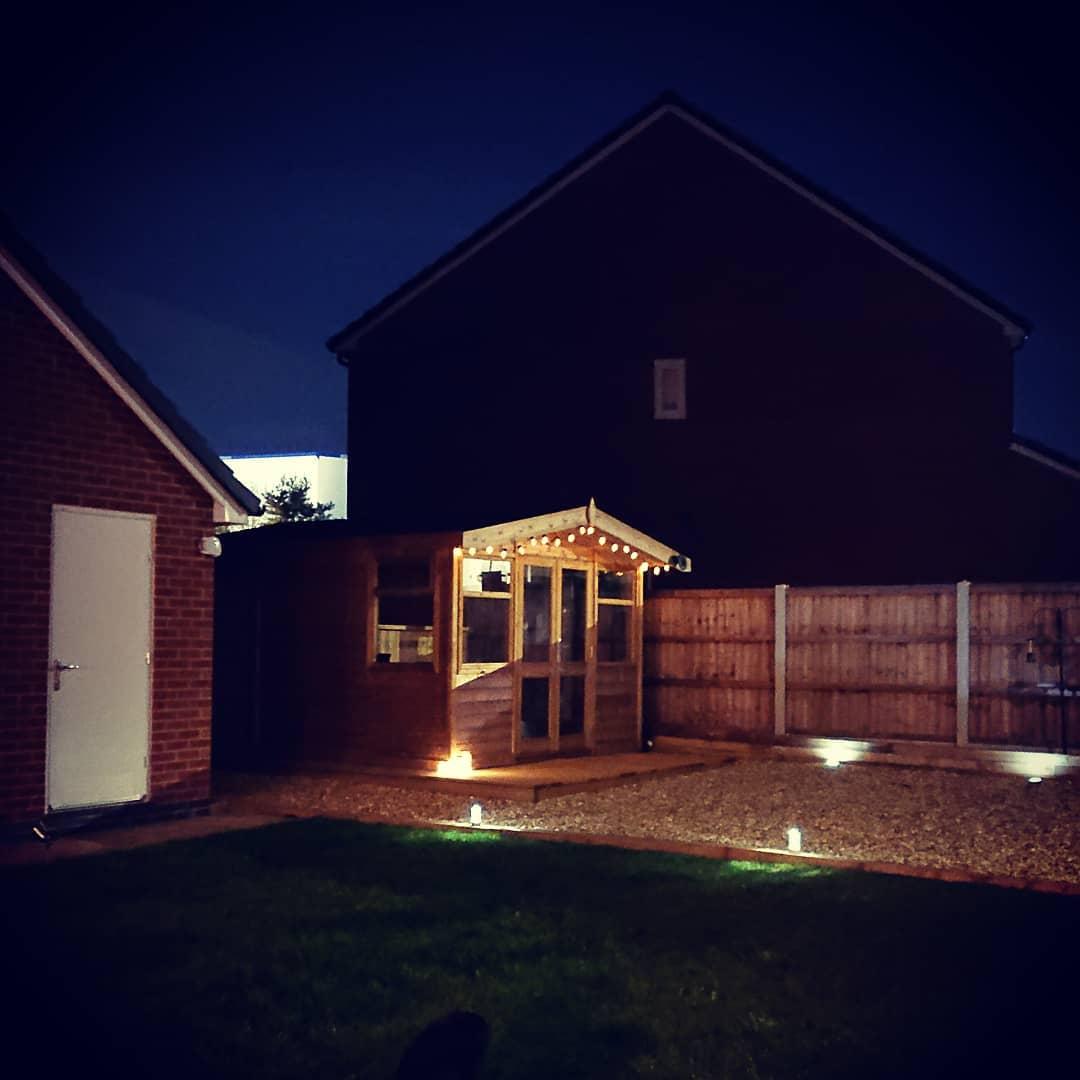 A wooden garden shed-cum pub at night, light by spotlights and festoon lights