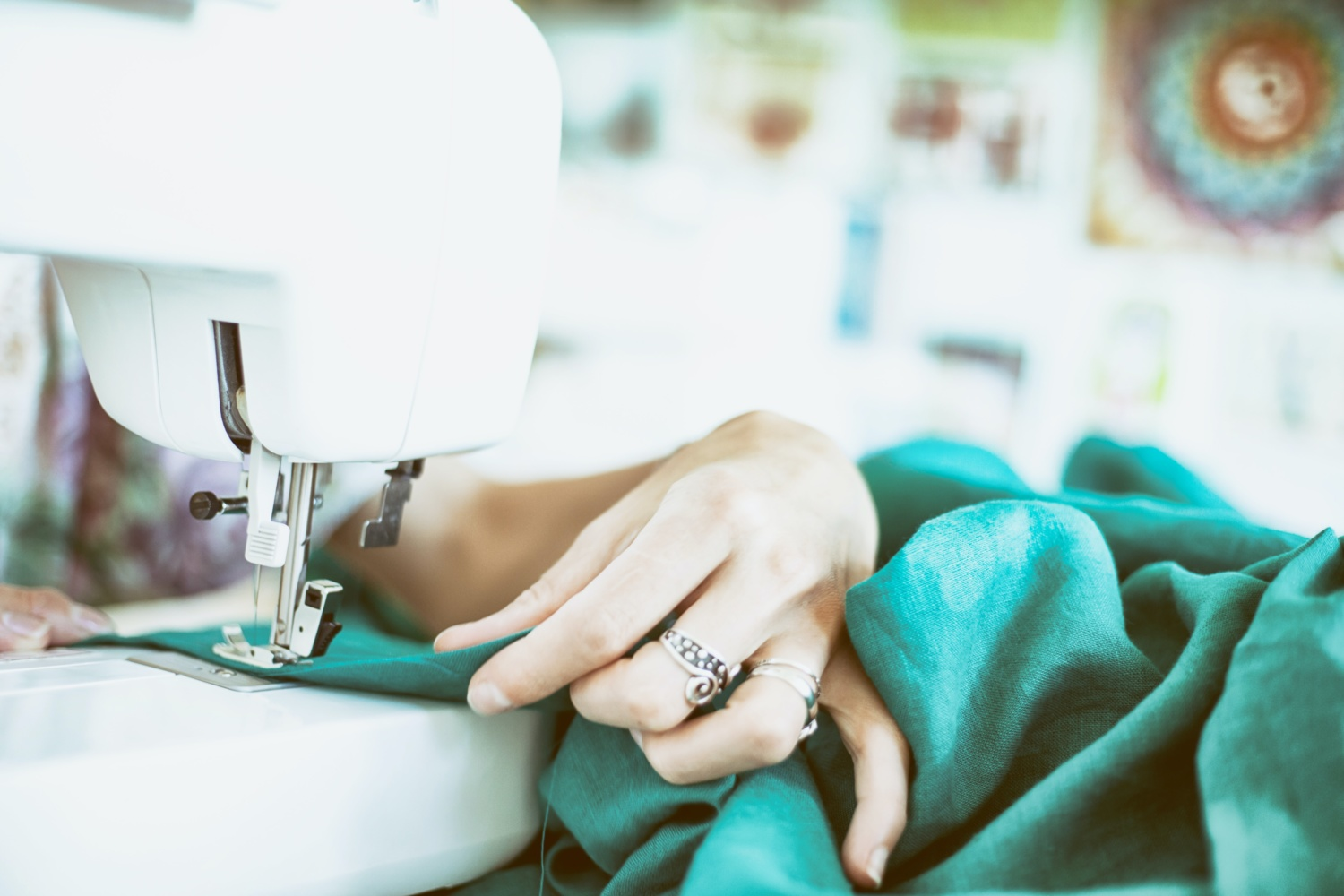 A close up shot of a persons hands sewing at a white sewing machine