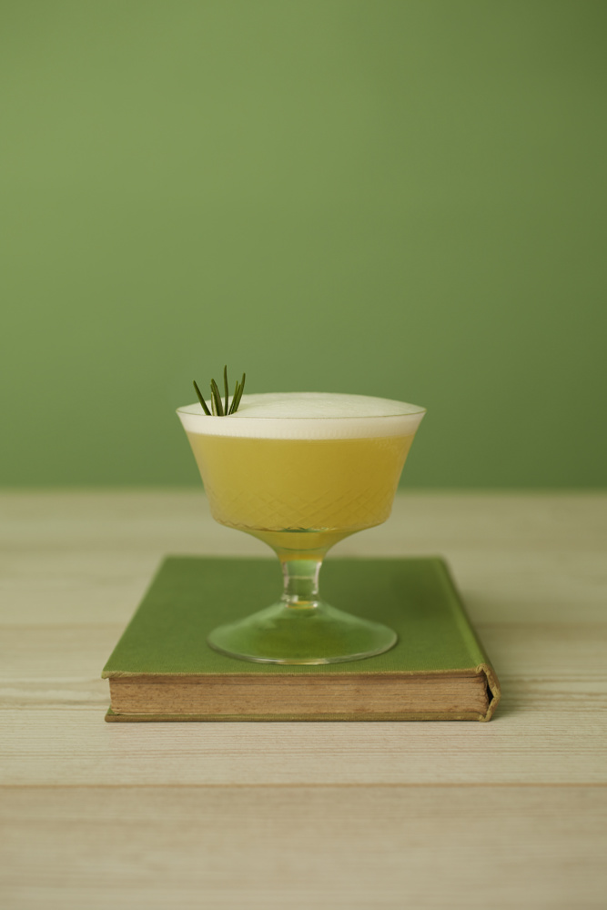 A frothy mocktail, garnished with a sprig of rosemary sits on an age green book on a wooden table