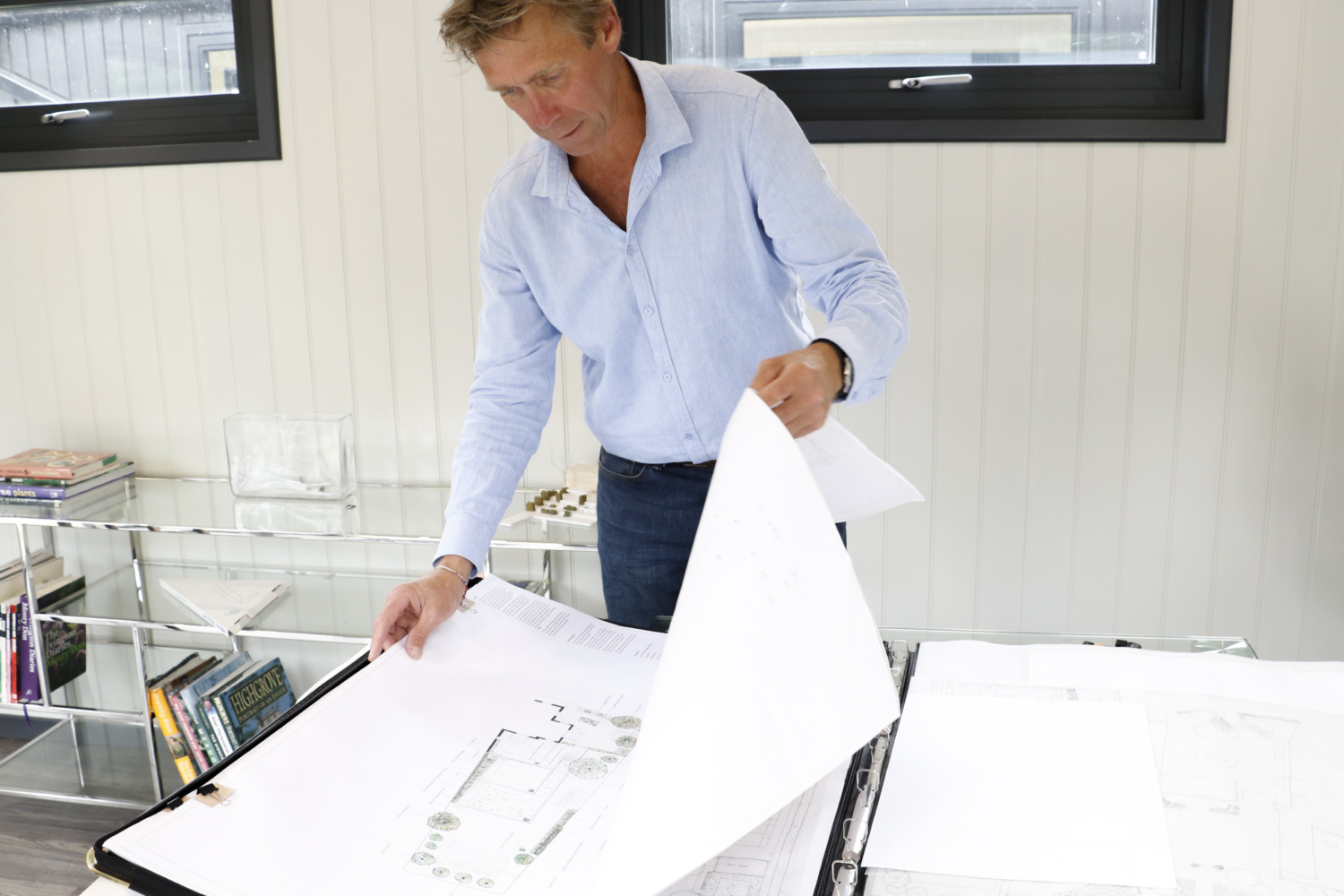 Tom Gadsby stands over a table and flicks through large sheets of paper that show plans of garden designs he has created