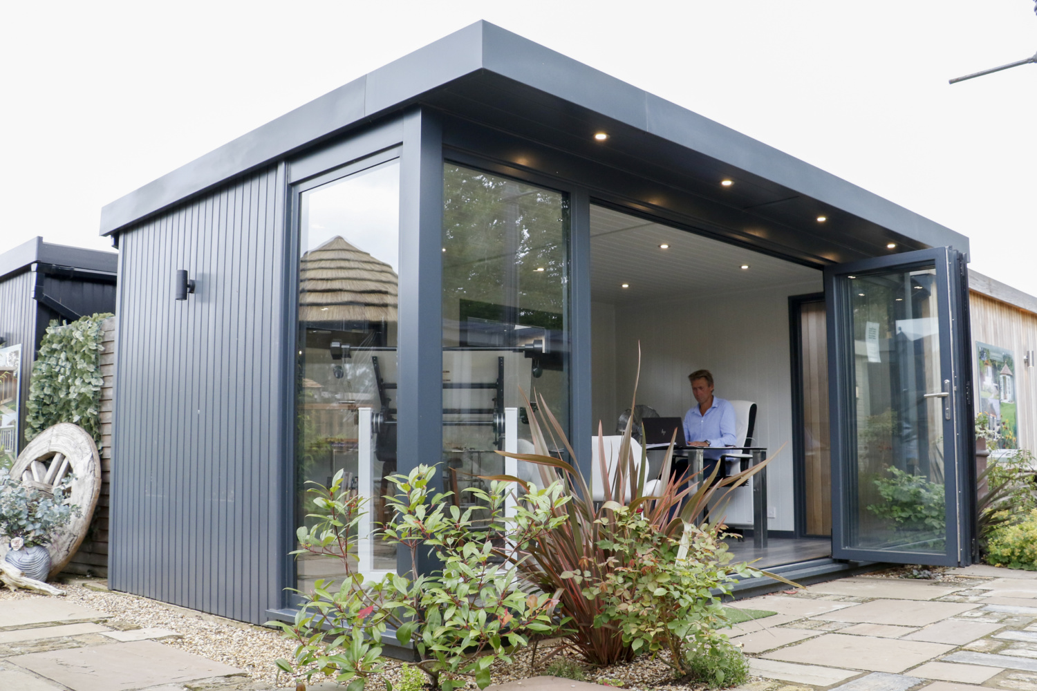 A contemporary garden office shows Tom Gadsby inside, sitting at a desk working. The garden office is painted wood with downlight along the front and planting at either side of the bifold door.