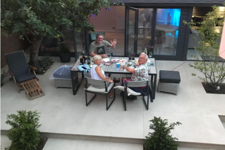 An arial shot of three people sat in the garden, around a table. All three are smiling at the camera, one is waving