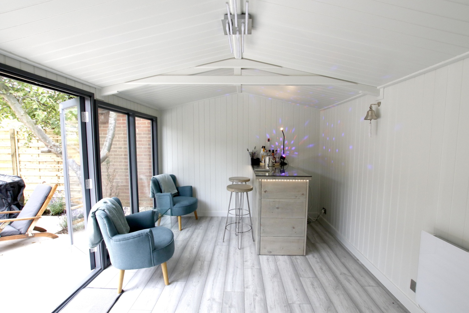 The interior of a wooden garden room, light and bright with two armchairs and a wooden bar and stool set. there are multicoloured disco lights